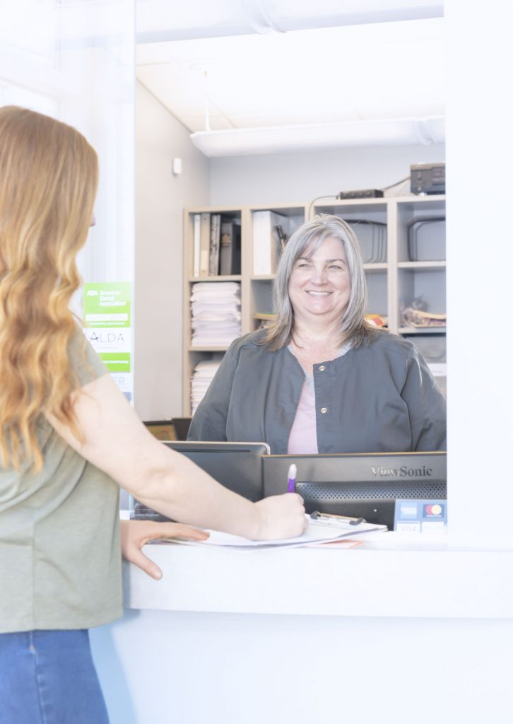 Receptionist at Deerfoot Dental smiles at patient who is filling out their dental paperwork
